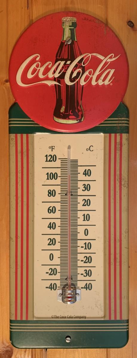 A metal Coca-Cola thermometer with Art Deco styling is mounted inside the trailer.