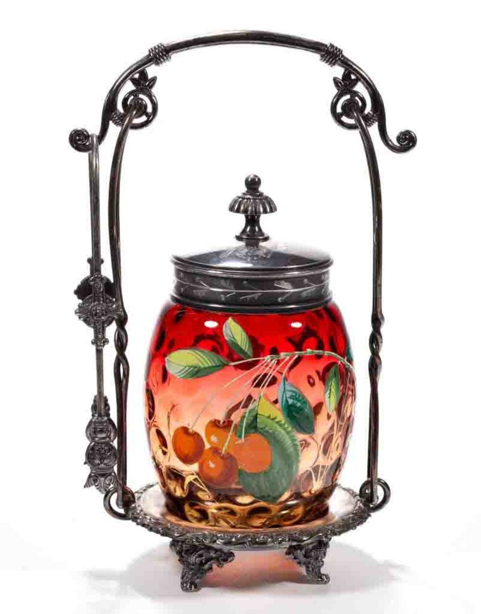 """Victorian spot-optic and enamel-decorated pickle castor, amberina with polychrome-enamel decoration, ovoid-form insert with cherries decoration, fitted into a quadruple-plated stand marked for """"MERIDEN"""" and numbered """"283,""""with tongs and cover. Maker unverified, possibly Phoenix Glass Co., fourth quarter 19th century, stand: 9-3/4"""" h, insert 4 -5/8"""" h; $400."""