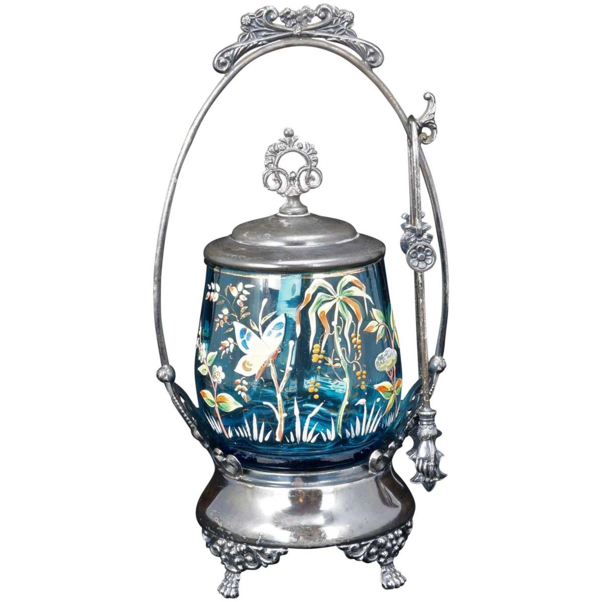 """Silver-plate pickle castor with blue-enameled art glass insert, c1870, in an Aesthetic Movement pattern with paintings of flowers and a pretty butterfly.  The top of the frame has a floral bouquet tied at the middle and the feet are decorated with arabesques and florid designs and have little paws, which coordinate with the hands at the ends of the tongs used to grab the pickles. The lid with an ornate finial fits the jar perfectly. The underside of the frame reads, """"M. S.BENEDICT M.F.G. CO. QUADRUPLE PLATE"""" and the number 264. Frame measures 10-1/4""""h x 5"""" w x 4-1/2"""" dia; glass measures 4"""" dia; $280."""