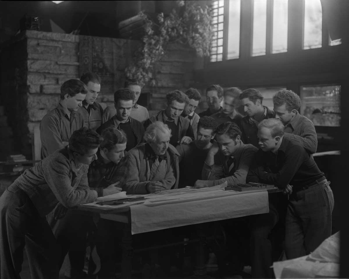 Frank Lloyd Wright (1867-1959) at a drafting table with several onlookers at Taliesin East, in Spring Green, December 1937.