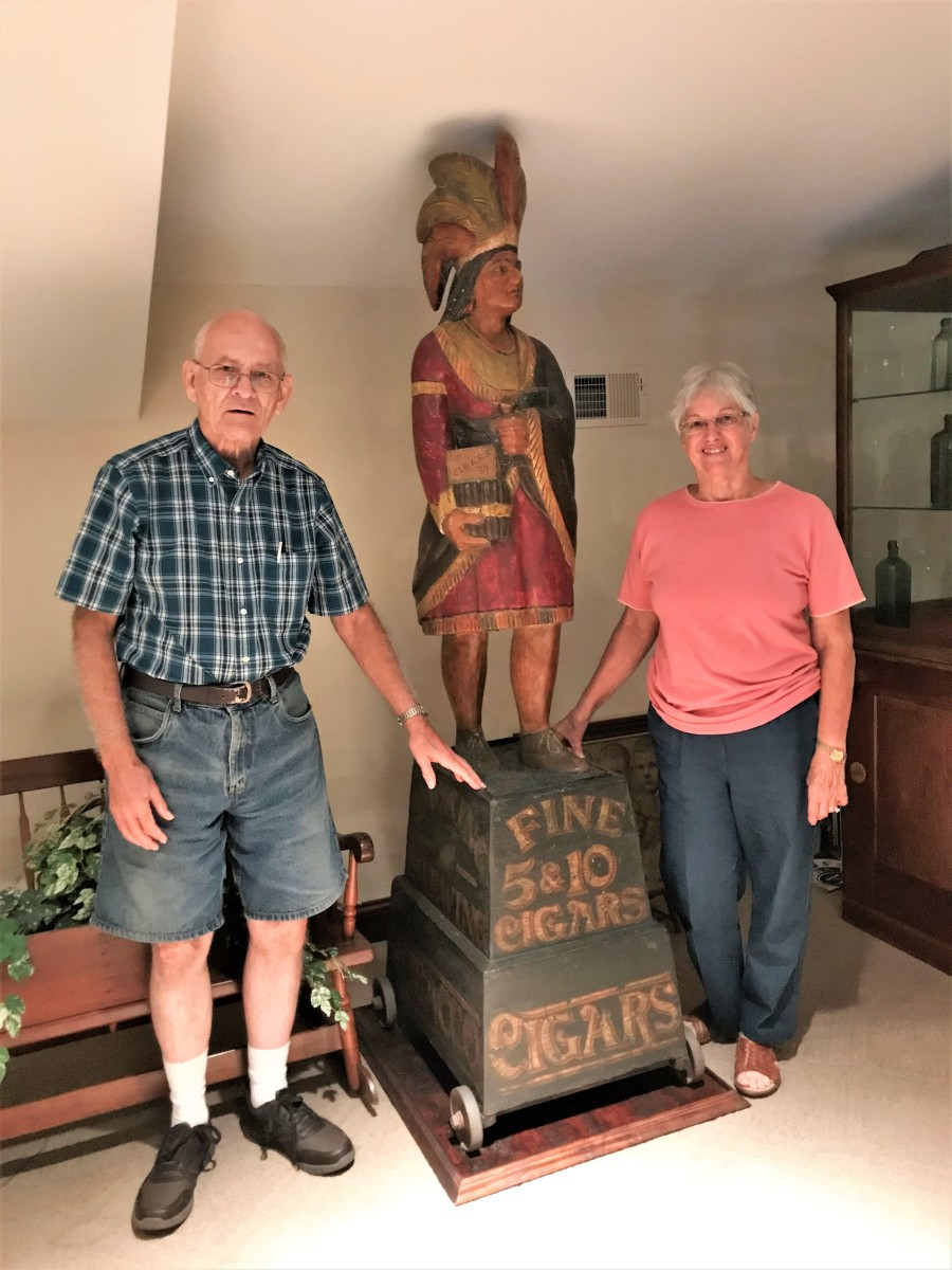 Jerry and Imogene Phelps with a late-19th century carved wooden cigar store Indian, part of his 10,000-piece antique advertising collection.