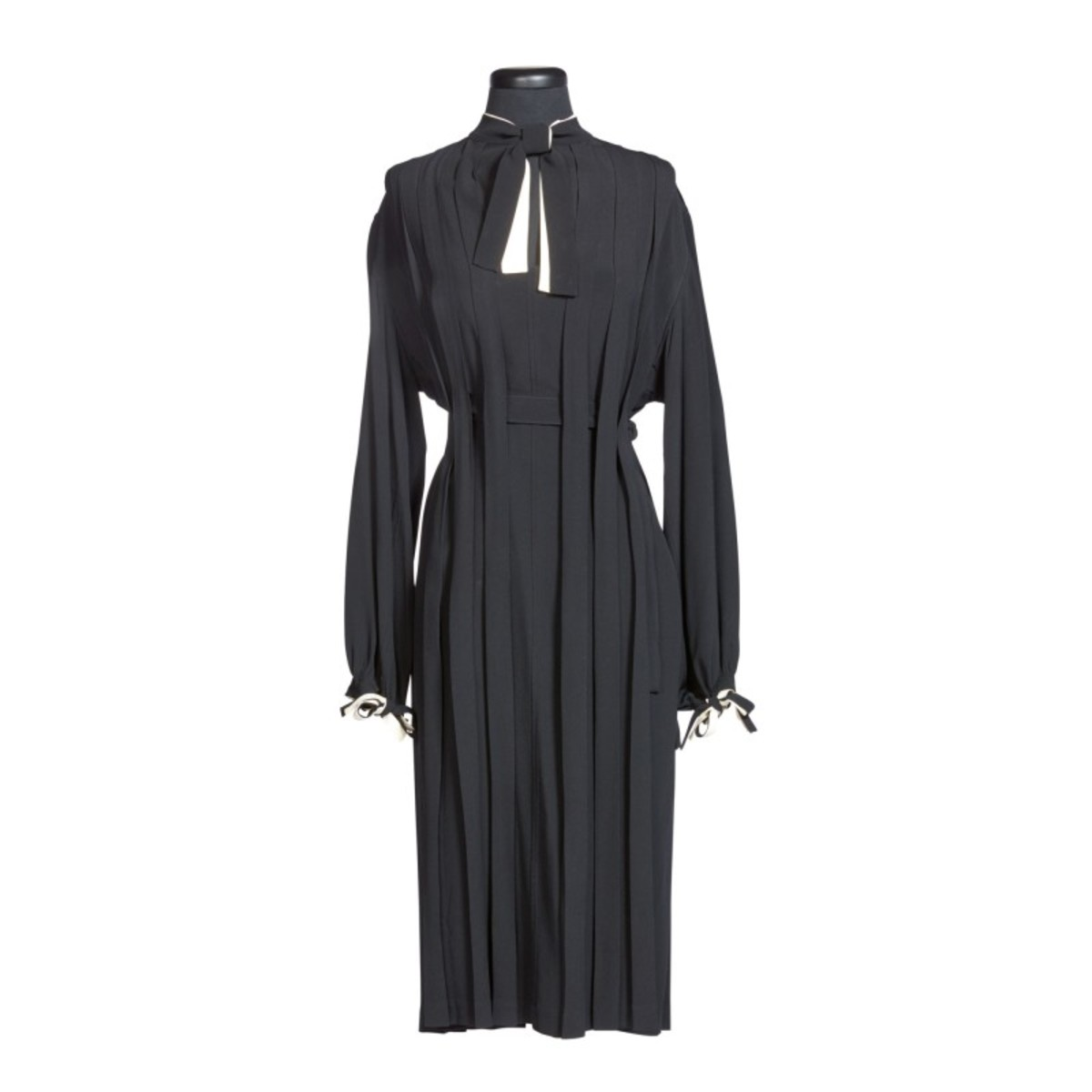 A custom pleated silk dress with twin stand up collars in black and white, long black and white ties to neck and wrists, adjustable black silk belt interlaced through concealed holes in pleats, possibly hand-sewn by O'Keeffe; sold for $25,000.