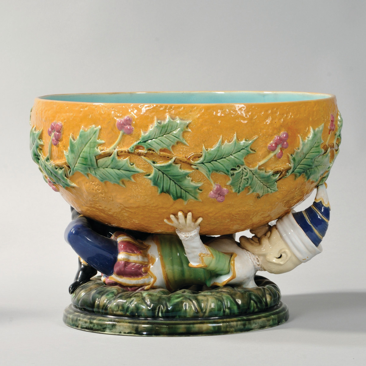 Majolica punch bowl from George Jones, England, circa 1870, with reclining figure of Punch  holding textured orange ground bowl with holly and berries.