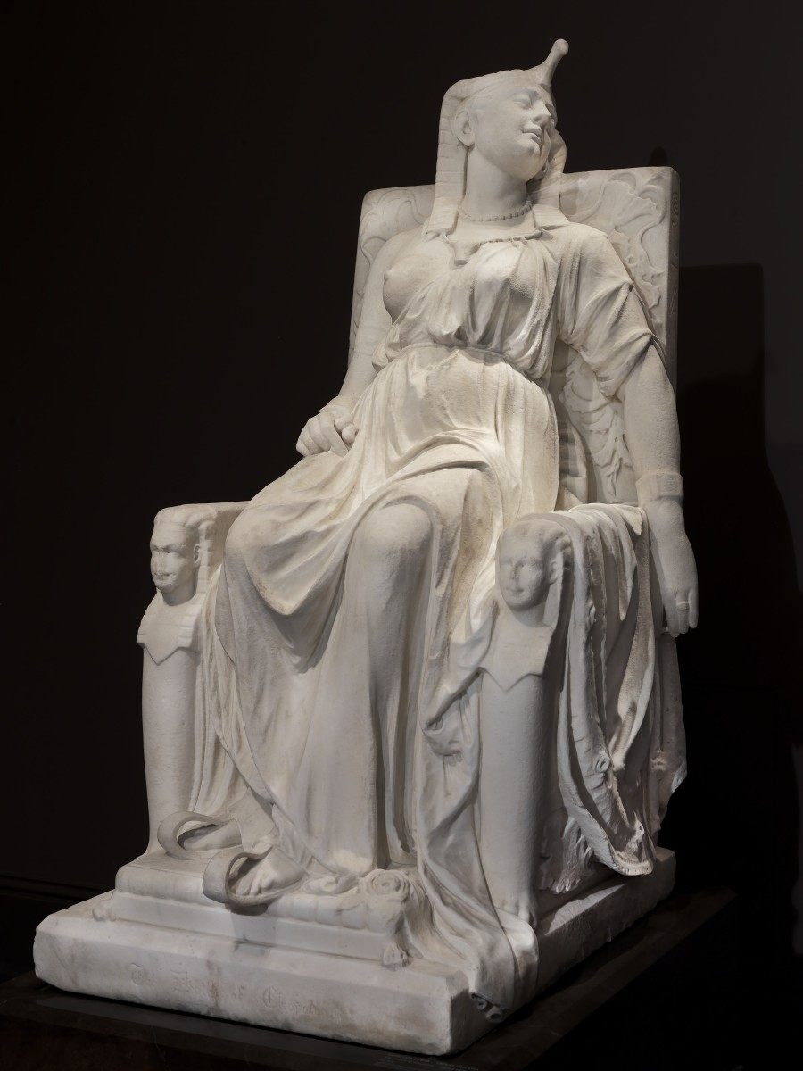 """""""The Death of Cleopatra,"""" carved 1876, marble, 63"""" x 31-1/4"""" x 46"""", now in the Smithsonian American Art Museum. The legendary queen of Egypt is often best known for her dramatic suicide, allegedly from the fatal bite of a poisonous snake. Here, Lewis portrayed Cleopatra in the moment after her death, wearing her royal attire, in majestic repose on a throne. The identical sphinx heads flanking the throne represent the twins she bore with Roman general Marc Antony."""