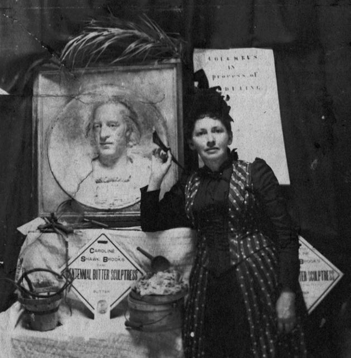 Caroline S. Brooks with a butter sculpture bas-relief of Columbus that she created for the 1893 Columbian Exposition in Chicago. She holds a butter paddle, one of her standard tools.