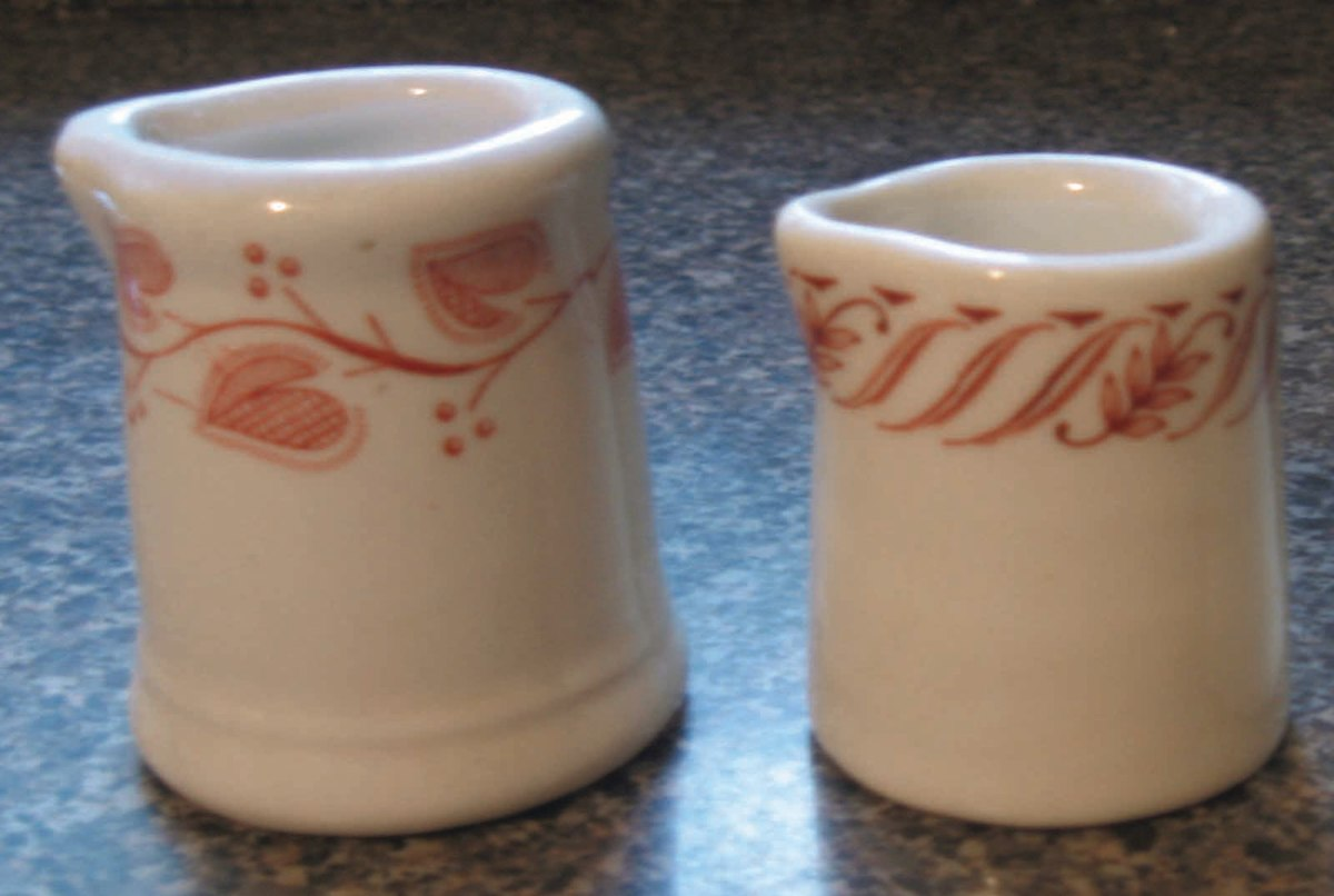 Two creamers with leaflet and petal designs around the rims.