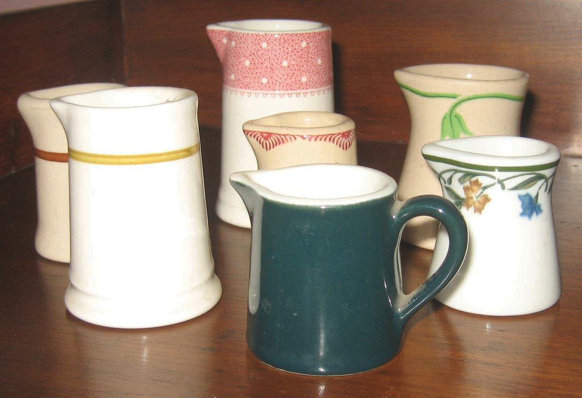 Assortment of seven vintage creamers. The deep green example with handle is actually a cream pitcher.