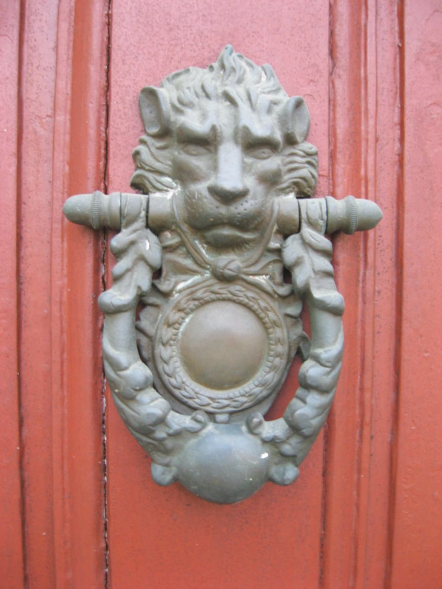 This knocker has the elongated design of a lion's head, along with a ball at the base, and is on the front door of an antique home in Deerfield, Mass. Although many door knockers welcome people to your door, this lion does not look particularly inviting or friendly.