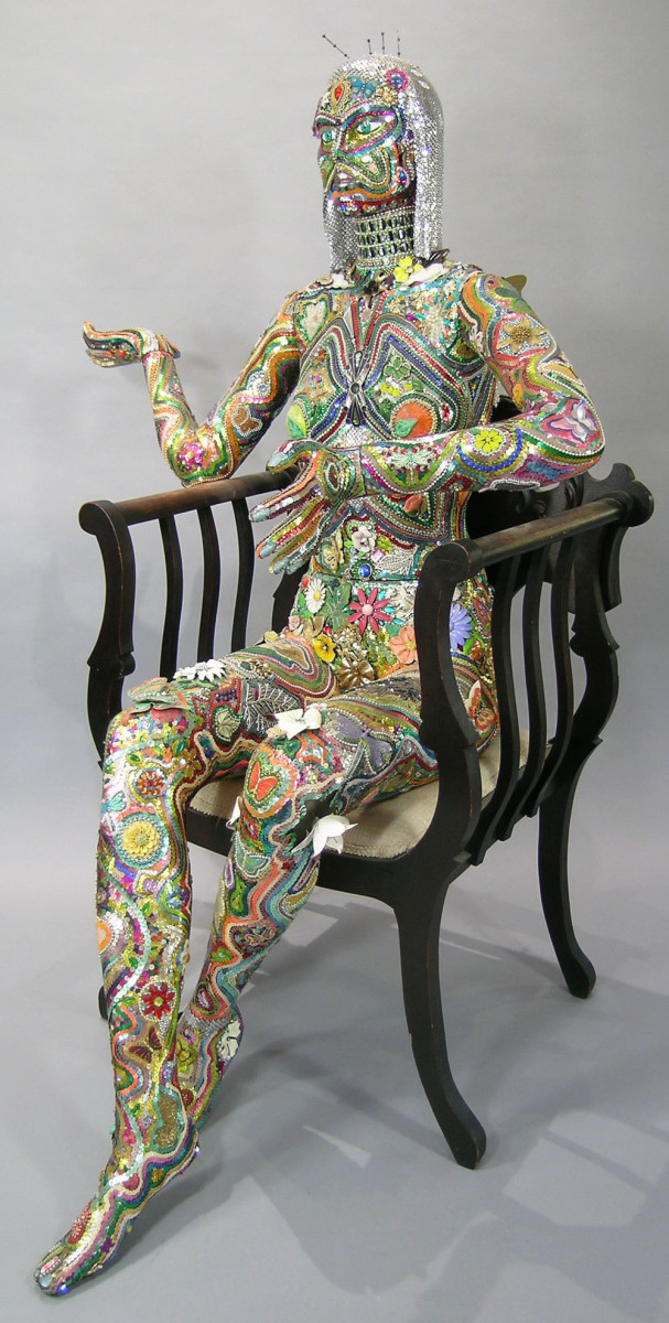 A rare full-size female mannequin covered in jewels and sequins, with butterflies, flowers, wings and leaves, seated in an antique chair, 20th century; estimate: $3,000-$5,000.