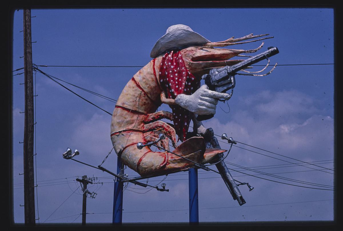 A pistol-packin' cowboy shrimp is the mascot of  Christie's Restaurant, Houston, Texas, 1983.