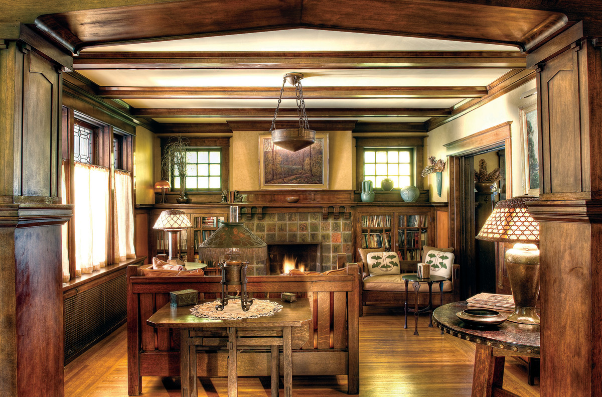 Dark woodwork, beamed ceiling and built-ins, muted tile, earthy colors, pottery, and nature motifs make this the quintessential Craftsman room as promulgated by Stickley. Oak furniture is early Stickley, including the ca. 1901 slatted crib settle and a leather-top library table, ca. 1902.
