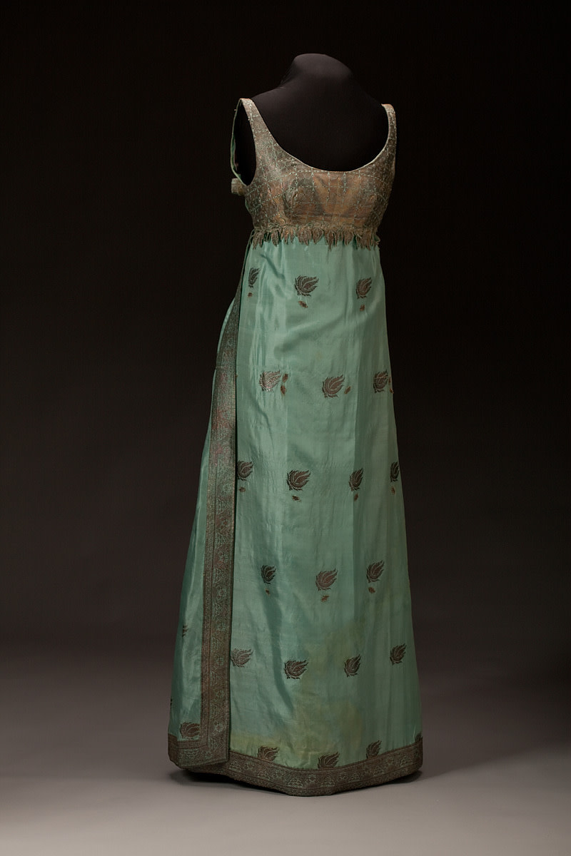 Pale green teal silk sari gown designed by Ann Lowe. The bodice is sleeveless with a scooped neckline and an empire waist. It is made from the border section of a sari featuring heavy metallic brocade in a geometric design, with the embroidered leaves from a sari border fussy cut from the fabric and sewn around the waist line, the bottom edges left loose to create a three-dimensional detail; 1966-67. Worn by Barbara Baldwin Dowd.
