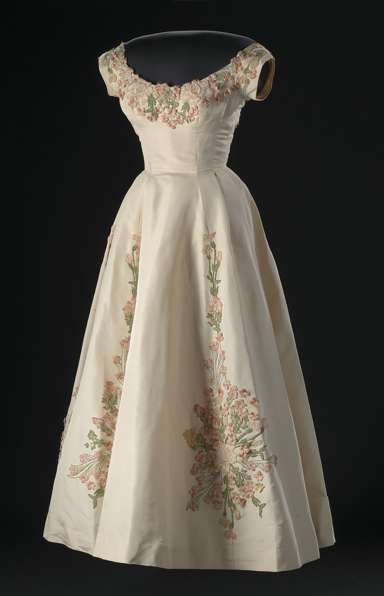 A cream silk faille dress with embroidered floral appliqué decorations designed by Ann Lowe. The dress has a bodice with cap sleeves, a scoop neck front, and a deep scoop neck back. Designed in 1958 and worn by Patricia Schieffer, wife of journalist Bob Schieffer.
