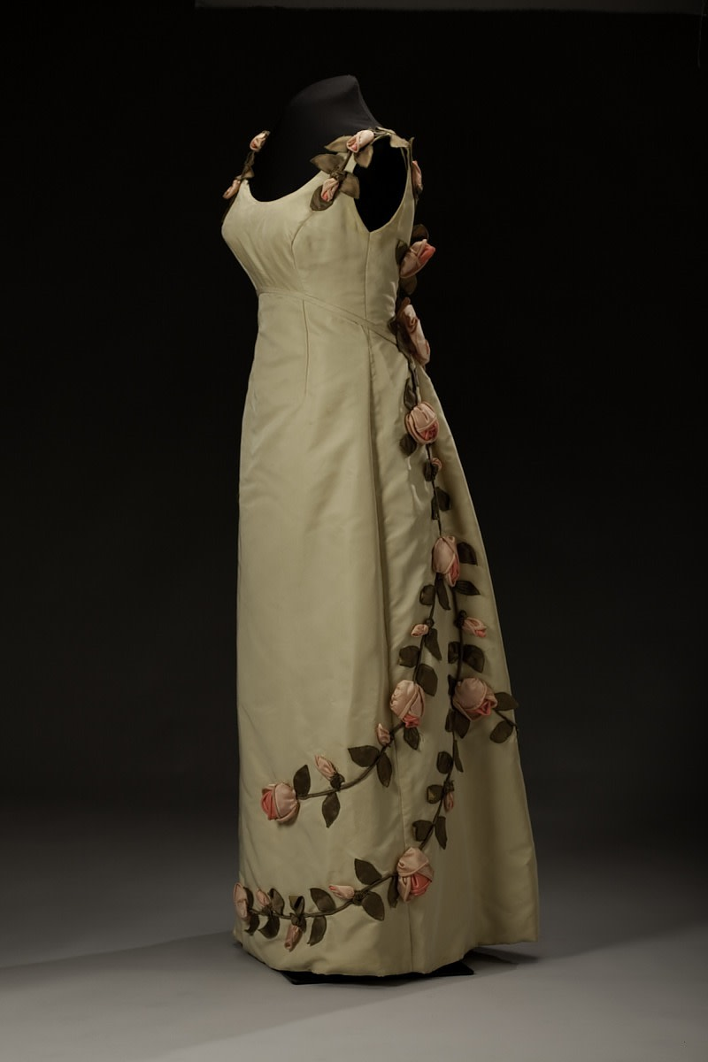 """An ivory dress decorated with swirls of handmade fabric rose vines, designed by Ann Lowe. The variety of rose depicted on the dress is the American Beauty, which has led to it being called the """"American Beauty"""" dress. Made in 1966-67 and worn by Barbara Baldwin Dowd."""