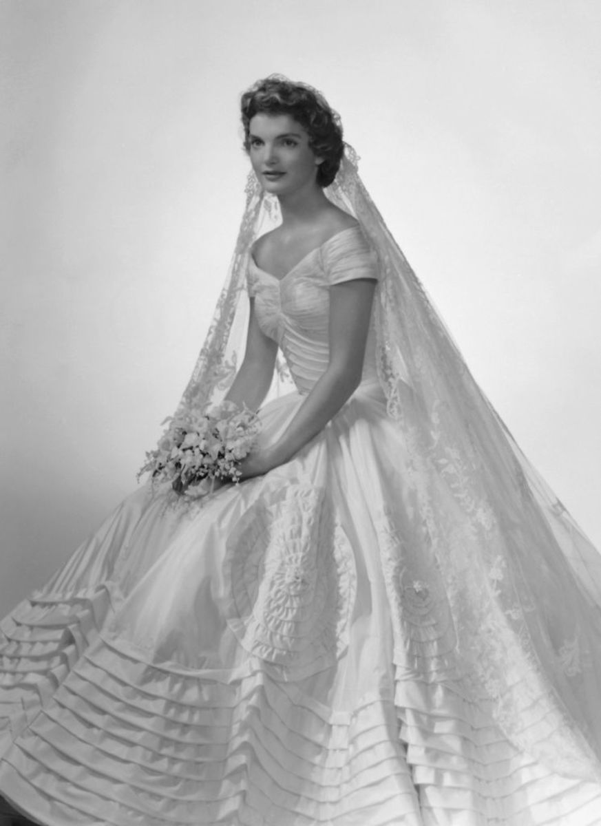 Bridal portrait of Jacqueline Lee Bouvier in the Ann Lowe-designed wedding dress, a bouquet of flowers in her hands, New York, 1953.