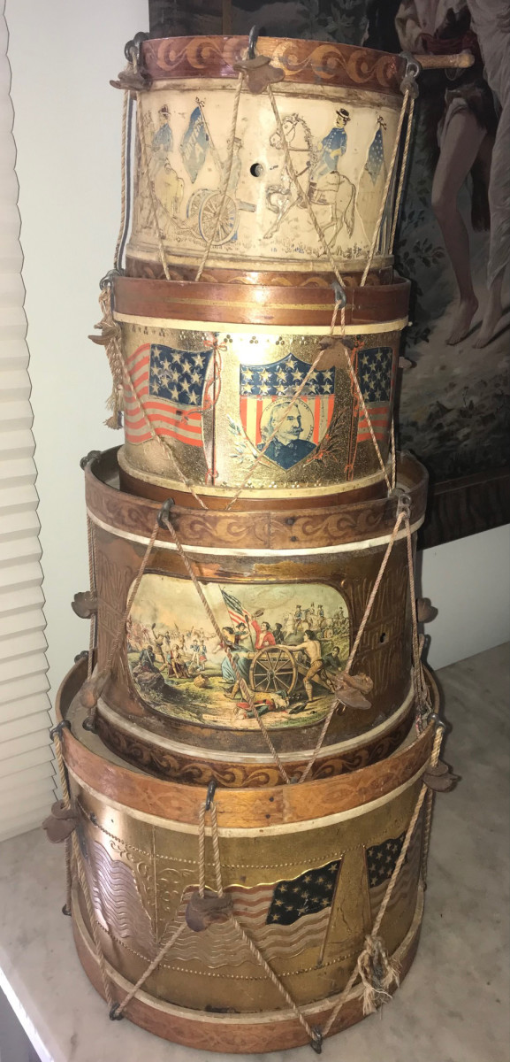 A stack of tin litho toy drums with stars and stripes, battle scenes and soldiers creates an interesting display.