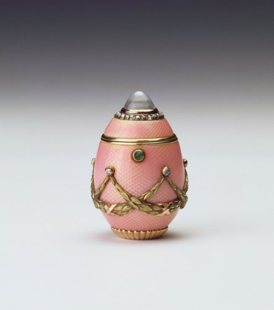 """This egg-shaped box of two-color gold and pink guilloché enamel was made by Carl Fabergé, c. 1900; 1-1/2"""" x 1"""". The lid is set with a domed rock crystal with a surround of rose diamonds and the body is hung with crossed yellow gold laurel swags suspended from rose diamonds. The egg has a cabochon emerald thumb piece and a gadrooned base. Fabergé produced boxes, pendants and even cups in the form of eggs and there are numerous examples of these objects in the Royal Collection."""