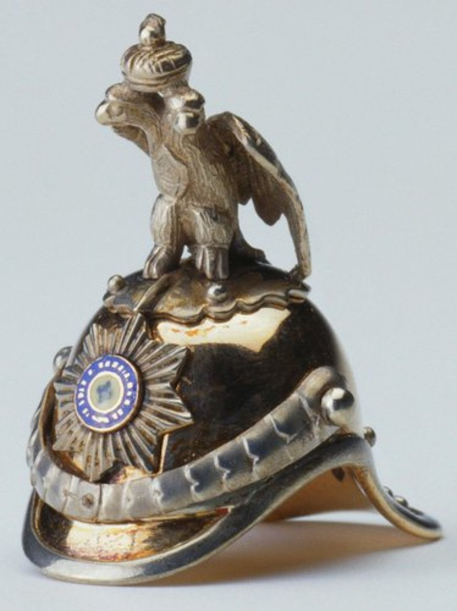 """Fabergé made numerous objects with military associations, often as presentation pieces. Helmets were produced as drinking vessels, although this miniature version made before 1896 by Erik August Kollin is far too small to have been intended as a functional object. It is a helmet of the Imperial Chevalier Guard and is enameled on the front with the star of the Order of St Andrew. The helmet is surmounted by the imperial eagle; 1"""" x 1"""" x 1/2""""."""