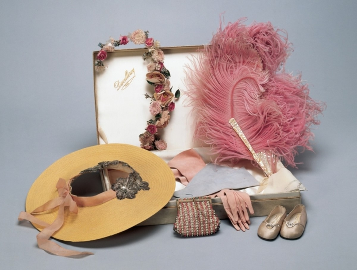 This group of tiny fashion accessories includes a pair of pale pink silk slippers with two silver buttons on the front of the shoe joined with a silver link and cut-out moons, and leather soles stamped with crosses. These were a state gift to Princess Elizabeth and Princess Margaret Rose from the children of France during a state visit by the king and queen in 1938.