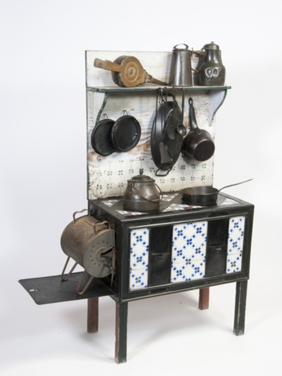 This model kitchen range from the 19th century is made of wood, iron, tin and enamel and features a painted wood back, purple and blue tiles and a back shelf to support the 13 miniature accessories and utensils.
