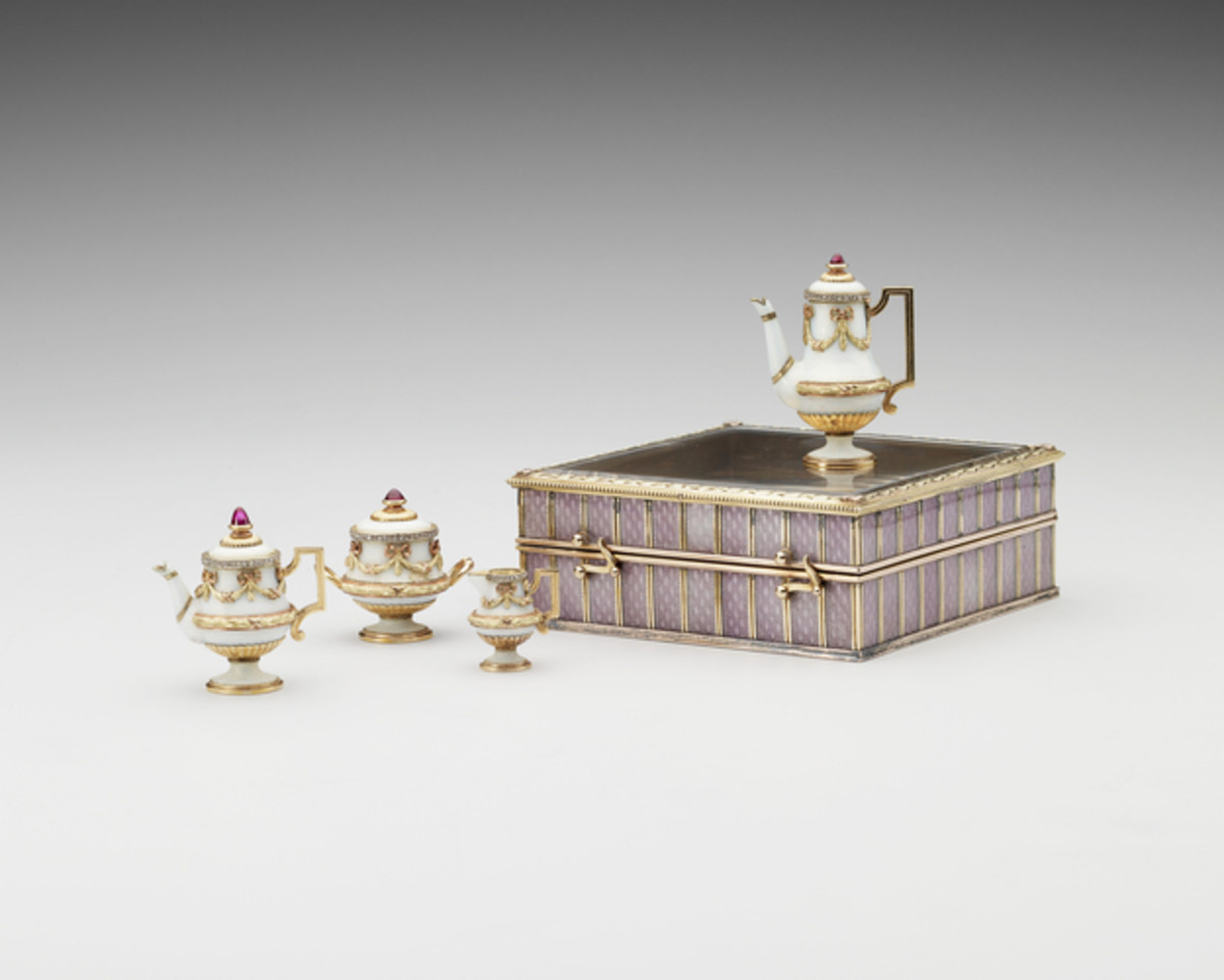 """This gold, crystal, enamel and ruby tea service was made by Carl Fabergé, 1896-1908; 1"""" x 2-1/2"""" x 2-1/2"""". Comprising a teapot, hot water pot, sugar bowl and milk jug, this tea set is of gold enameled in a pale opaque bluish-white, but there is no engine turning on the metal. This deliberately plain enameling creates the impression that the tea set is made of porcelain. The lids are each surmounted by a finial in the form of a cabochon ruby. The quality of the gemstones and the rich application of four colored gold decoration may indicate that this was an imperial commission. The box is of silver-gilt, applied with colored gold and with guilloché enamel in mauve, the favorite color of Tsarina Alexandra Feodorovna, which this belonged to, and the lid is set with a panel of crystal."""