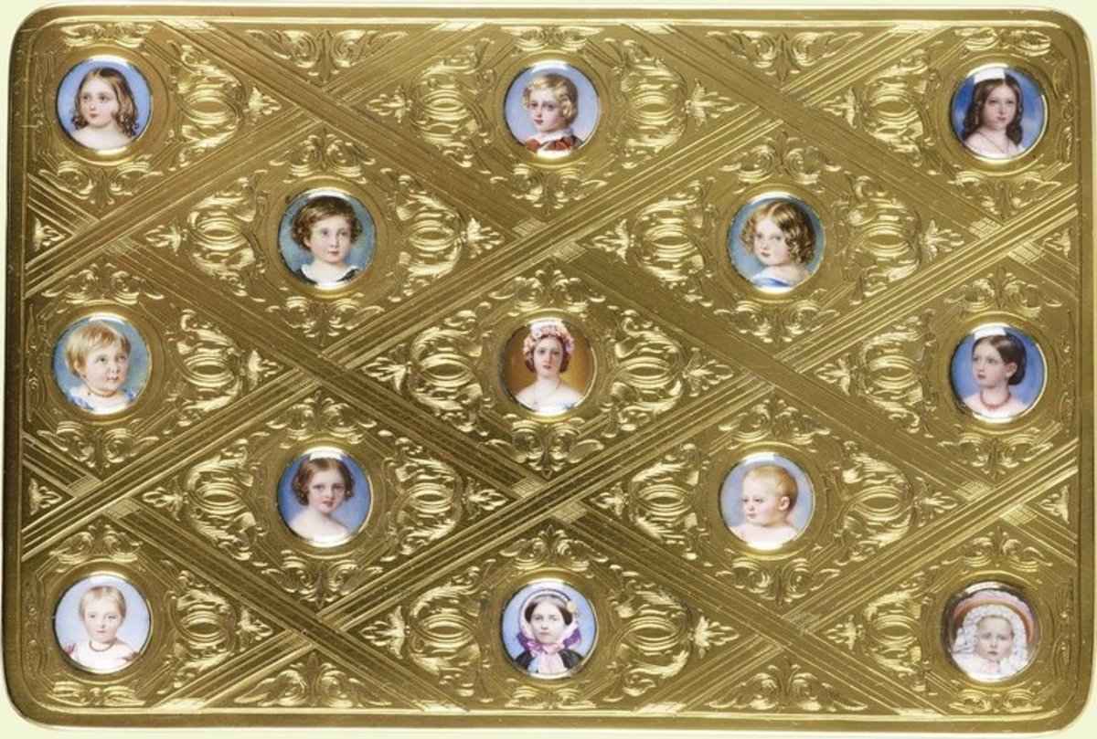 """This gold and enamel box, 1"""" x 5"""" x 3.3"""", features miniature portraits of Queen Victoria and Prince Albert Edward and their children Princess Alice, Prince Alfred, Princess Helena, Princess Louise, Princess Helena, Princess Louise, Prince Arthur, Princess Beatrice, and Victoria, Princess Royal. The enamel studs were given as gifts by Queen Victoria to Prince Albert in commemoration of their wedding anniversary in February 1859 and also on her birthday in May 1859."""