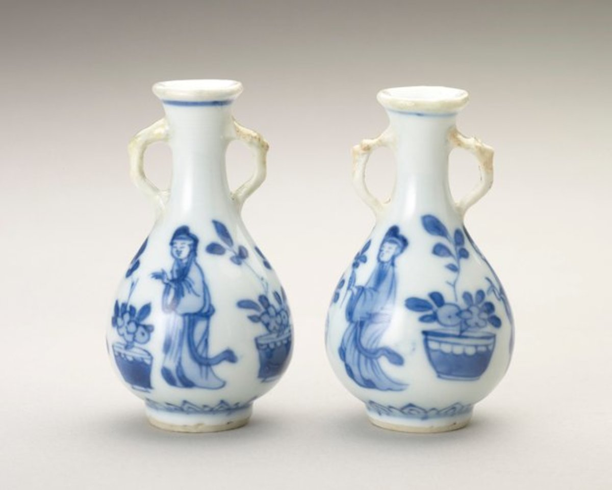 """Two blue-and-white miniature porcelain bottles painted in underglaze blue, Jingdezhen (Jiangxi Province, China), 1690-1700, about 3"""" h. Each pear-shaped, with tapering neck and spreading lip, the sides have a pair of animal-headed loop handles picked out in brown glaze. Painted in panels round the sides are three women tending flowers in pots, with a petal border below."""