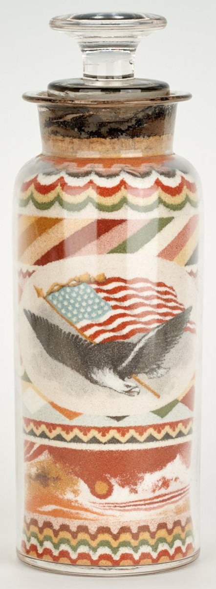 """Patriotic sand art bottle, dated 1889, filled with multicolored, layered sand in decorative stripe, swag and diamond patterns, one side with a vignette of a spread-winged eagle and 36-star American flag, the alternate side with a detailed floral vignette including forget-me-nots, roses and pansies, 6-5/8"""" h. This sold at auction for $55,000 against a high estimate of $12,000."""