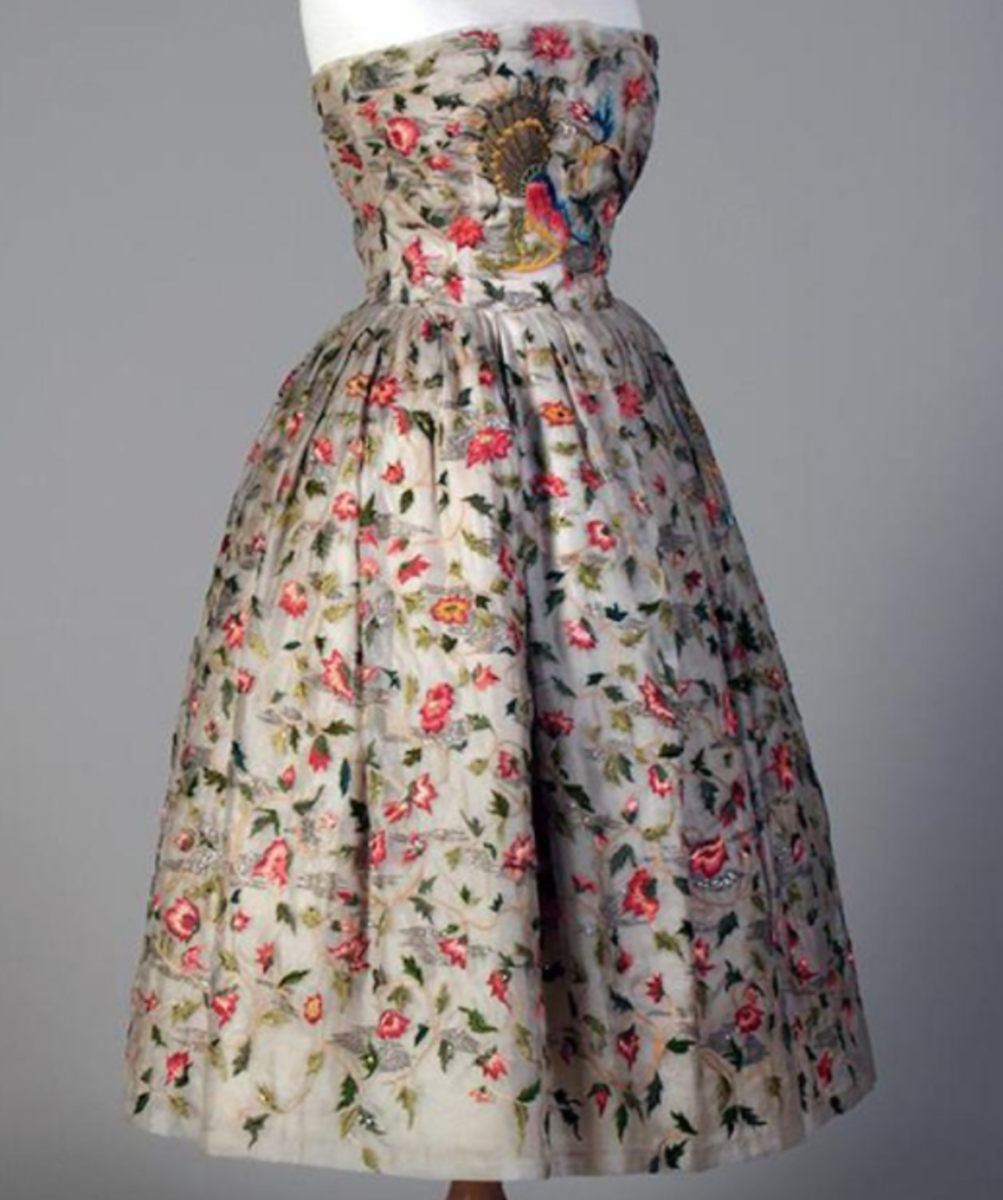 Trails of embroidered Elizabethian flowers in multi-colors and silver-gilt thread and sequins adorn a Christian Dior cocktail dress from spring 1956.