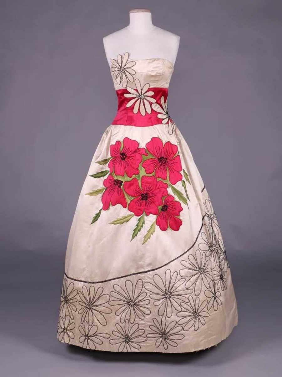A circa 1953 cream-silk strapless evening gown by Emilio Schuberth is overlaid with cream daisy appliqués outlined in black faceted and mini bugle beads, with a cerise satin poppy bouquet appliquéd to the front. This sold at auction for $3,000.