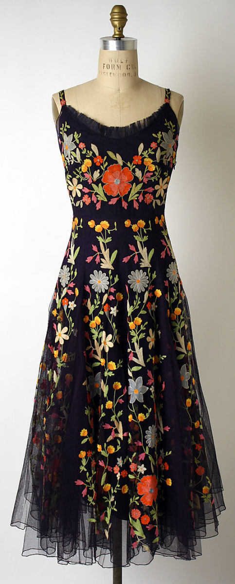 This 1940s Hattie Carnegie cocktail dress features black silk net with a twining garden of tambour embroidery in vermillion, peach, buttercup yellow, tangerine, celadon, spring green, and silvery blue.