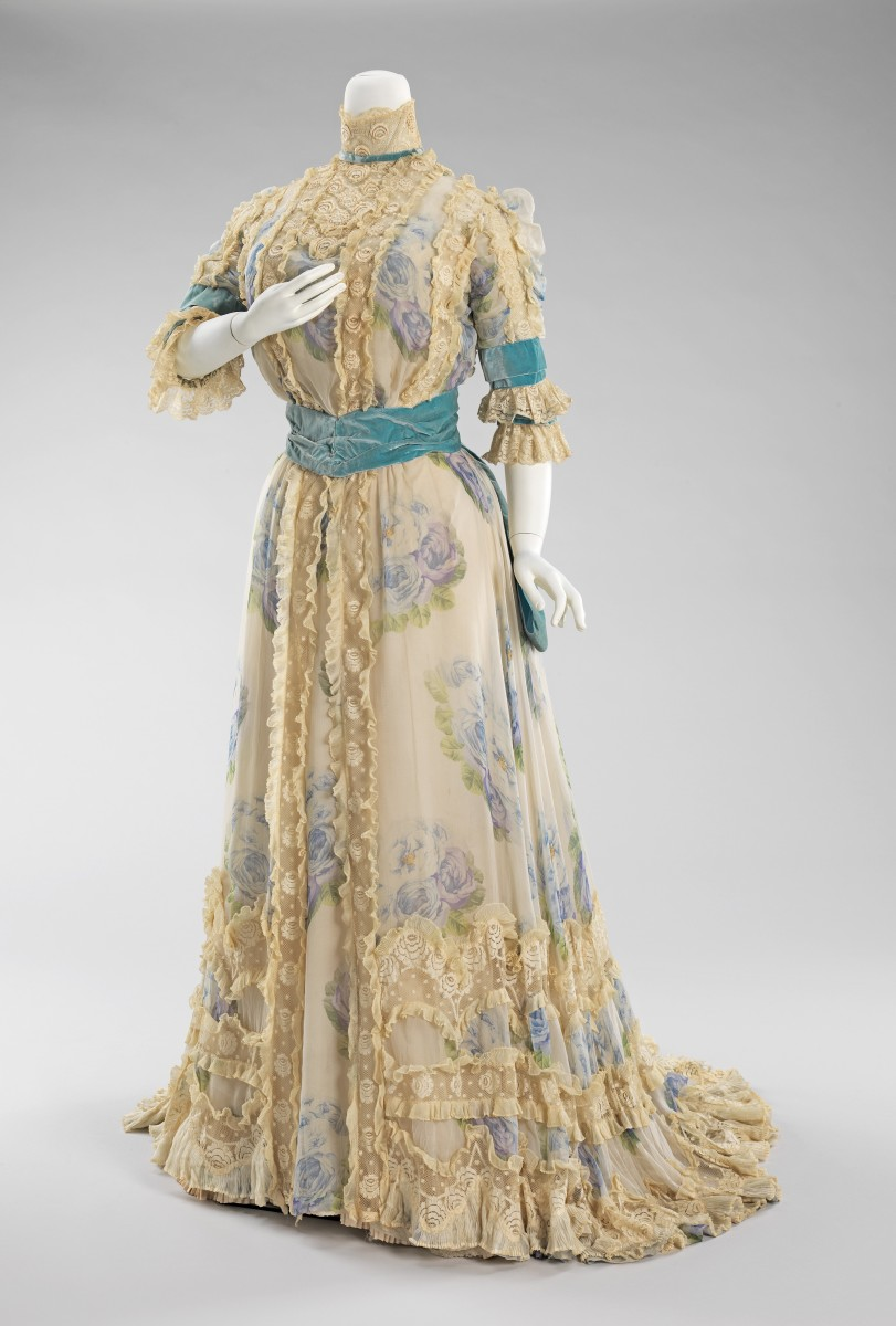 This elegant afternoon dress by Jacques Doucet, 1900-1903, is an excellent example of his penchant for lingerie-like garments, which is represented by the delicate ruffles and rose printed chiffon. The color combination of blues accented with turquoise is a favorite of the designer. This dress would have been suitable for afternoon events, such as the races and other promenade activities.