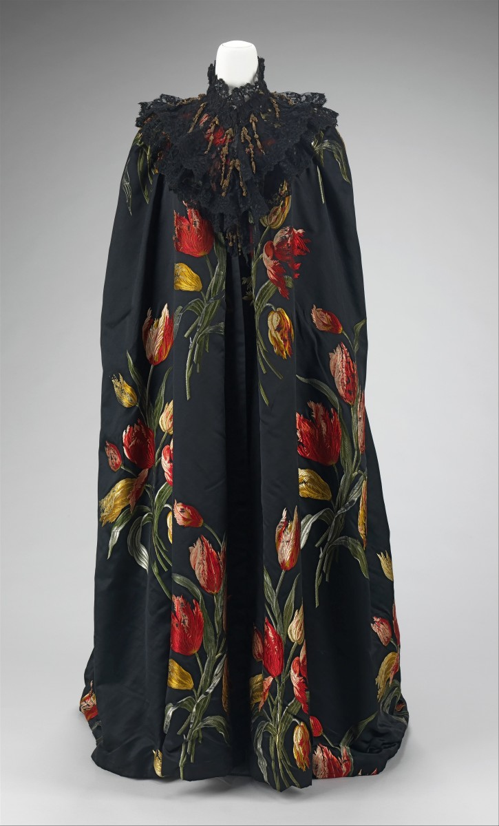 """Charles Frederick Worth was constantly interested in supporting the textile industry, as evidenced in this 1889 cape, which is designed to showcase its textile to the extreme. The textile itself has a repeat that is over three feet long, making it stunning but also extremely difficult to weave. The dramatic fabric, """"Tulipes Hollandaises,"""" was exhibited at the Exposition Universelle of 1889 in Paris to universal admiration and won a grand prize. The tulips have an aggressive dynamic quality about them with the brilliant, vibrant colors against the deep black background consistent with the seductive femme-fatale sensibility of the 1880s and 1890s."""