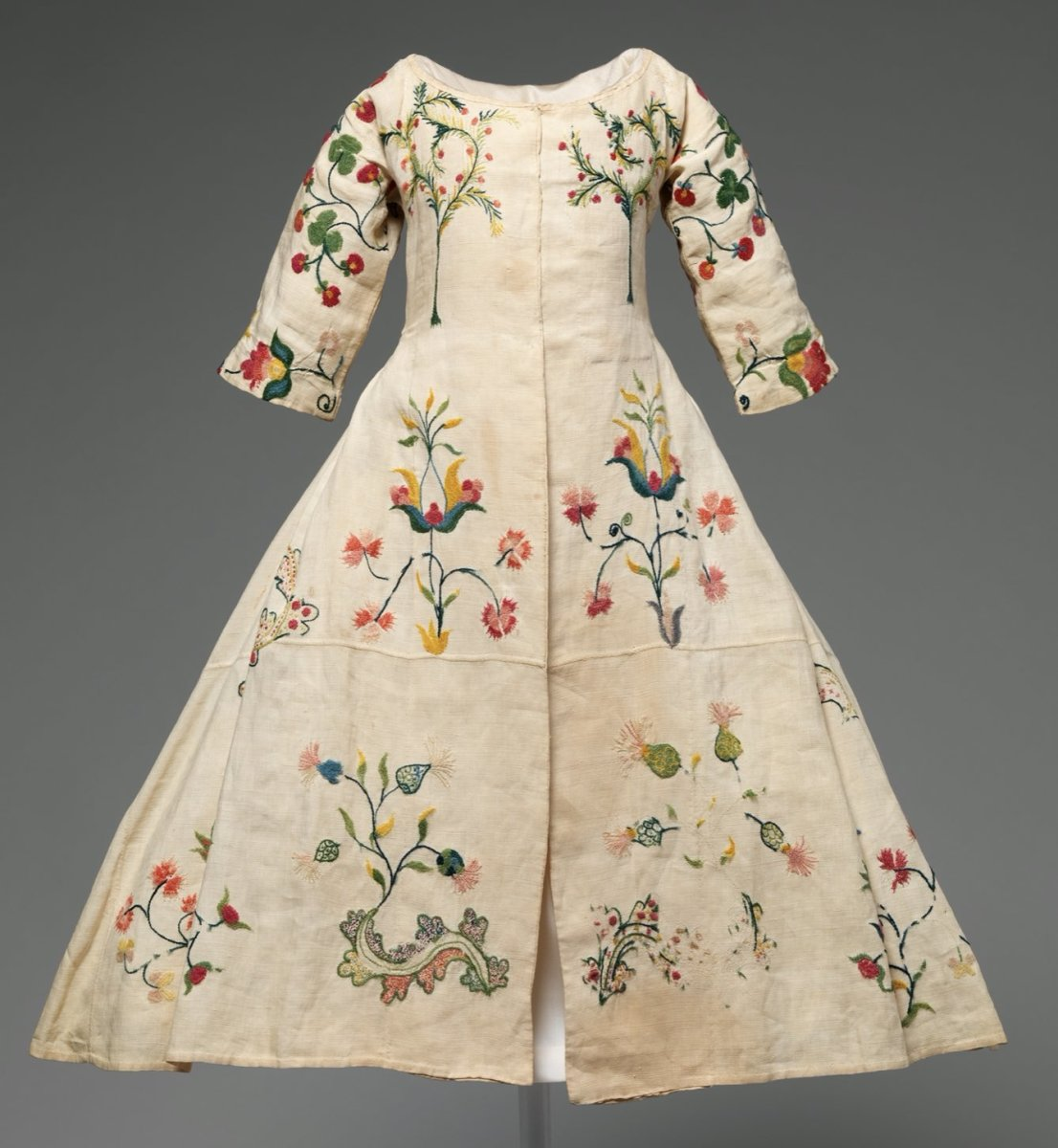 An American-designed child's dress from the mid-18th century has bright wool embroidered on linen of thistles and carnations and mimosa trees, full of hope and joy, with love and protection woven into each and every stitch.
