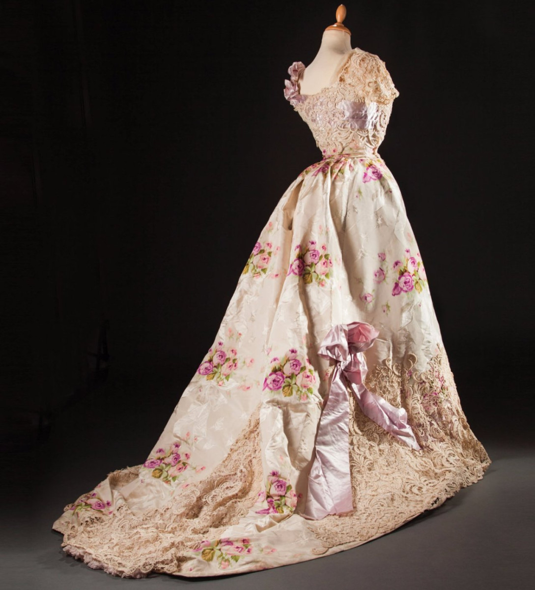 Large bouquets of pink and fuchsia roses decorate this circa 1890 silk evening dress by Madeleine Laferriere. Added to the ornamentation is an application of chemical Venice lace and a large iridescent mauve satin ribbon. This sold at auction for $6,700.