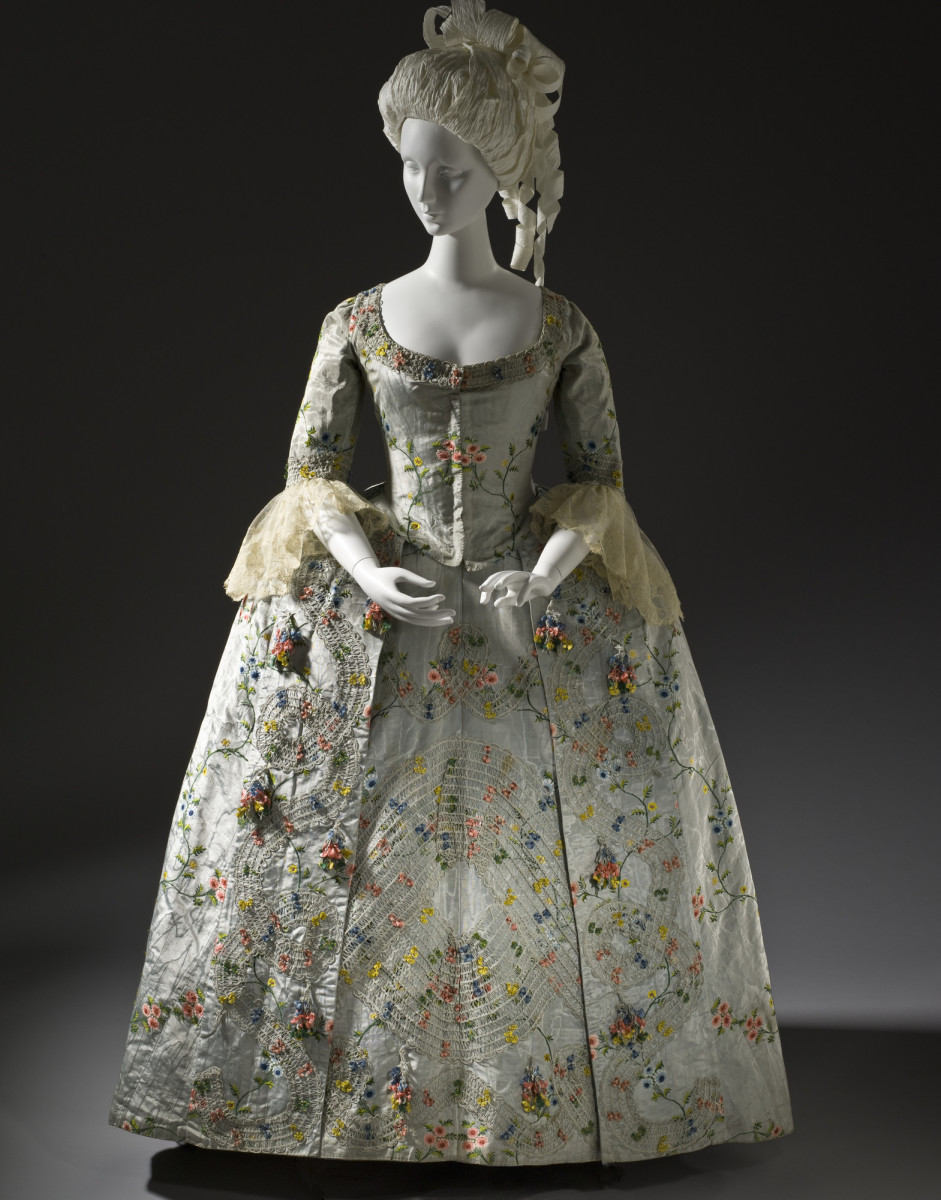 This robe à la française, circa 1775 and likely from the Netherlands, features elaborate passementerie and the 18th-century trend of silk fly fringe and braids with 3D texture, intermingling with delicate little bouquets of flowers. It would have taken hours upon hours of hand knotting cord into flies of silk to get this design and whoever did it was supremely talented.