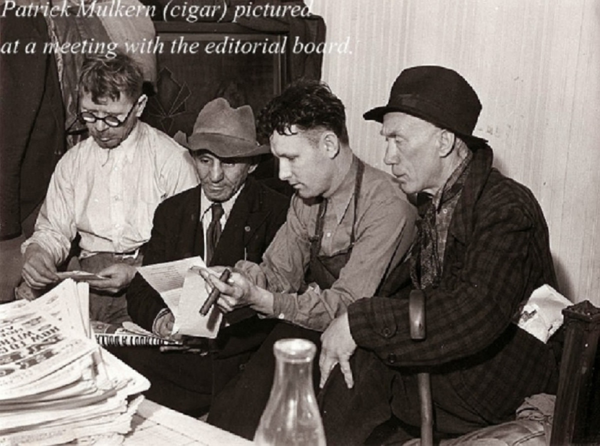 Hobo News Editor Pat Mulkern (second from right, with cigar) and his editorial team discuss business.