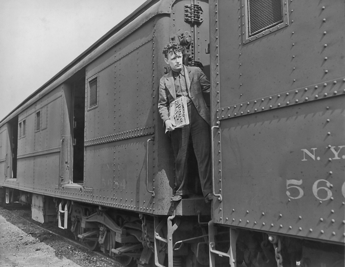 """Pat """"The Roaming Dreamer"""" Mulkern standing between freight cars with copies of The Hobo News, Hastings, New York, circa 1940."""