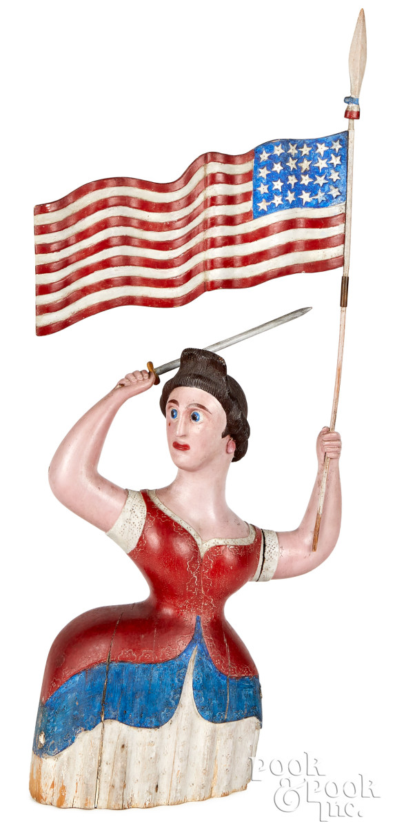 Important New Hampshire carved and painted Miss Liberty, ca. 1875, standing in a defiant pose with flag and sword raised, her blouse and dress with stamped edges, figure is 19-1/4'' h, base is 10'' w and overall height is 33''. Estimate: $100,000-$150,000.