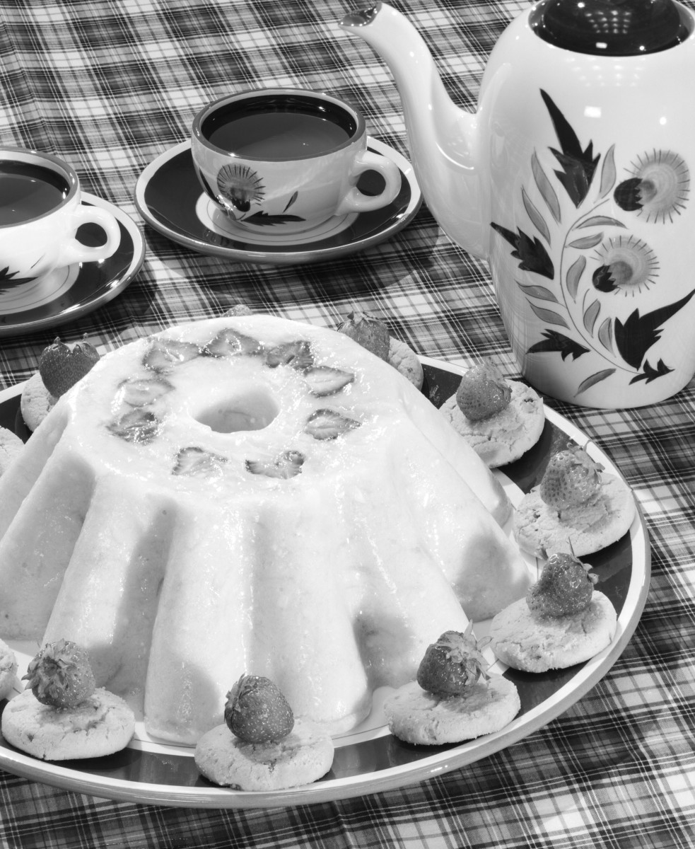 """Ready for coffee and dessert: One of the appealing things about gelatin molds and salads was that they made you the hostess with the mostess when you served one to company. This Jell-O mold from the 1950s features sliced strawberries inside and is garnished with whole strawberries perched on top of Pecan Sandies. The coffee pot and cups are by Stangl Pottery and in the """"Thistle"""" design."""