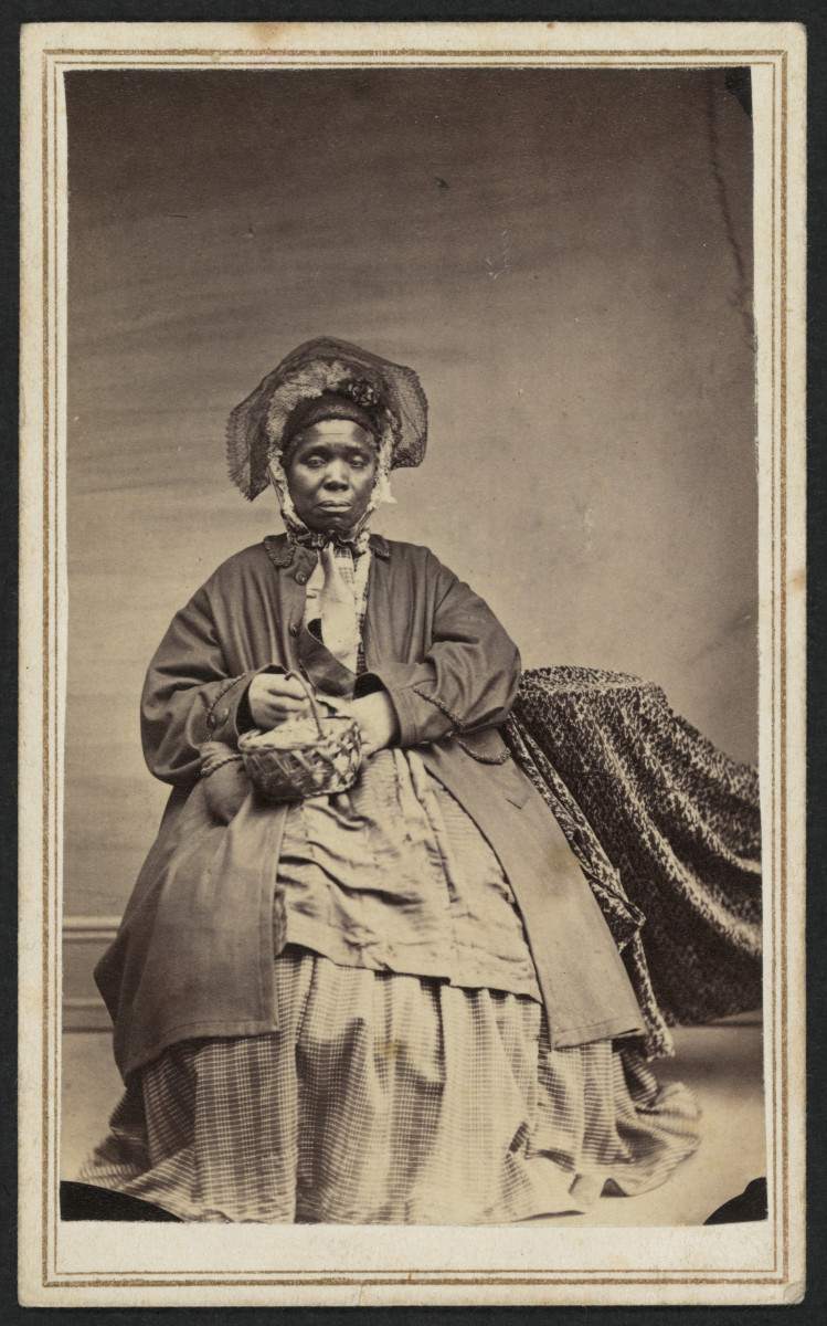 A carte de visite of a woman named Charlotte Scott holding a basket, circa 1864-1867. The canceled stamp on the back, shown below, is an orange 2-cent Bankcheck.