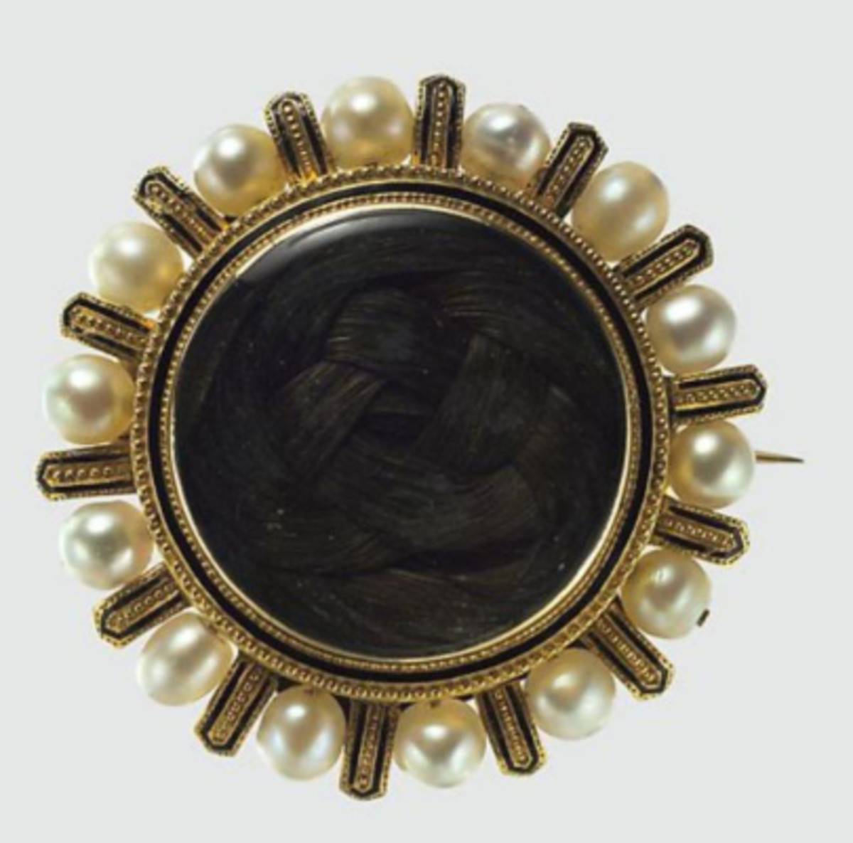 A mourning brooch by Tiffany & Co., 1868, gold, pearls, black enamel and hair.