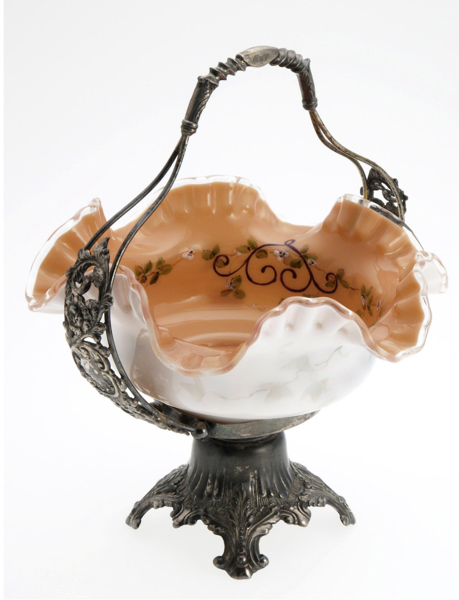 """American art glass bride's basket on Pairpoint stand, circa 1880, with a heavily ruffled rim, white exterior decorated with a faint ivy pattern, a salmon pink interior and enameled design of small white flowers, leaves and purple scroll work, silverplated footed holder with stylized floral handle, about 12"""" h; $890."""