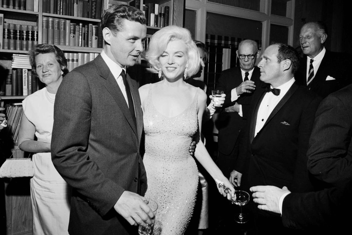 Marilyn Monroe in the dress she wore to sing for President John F. Kennedy, pictured with his brother-in-law Steve Smith, left, at a party after the event.