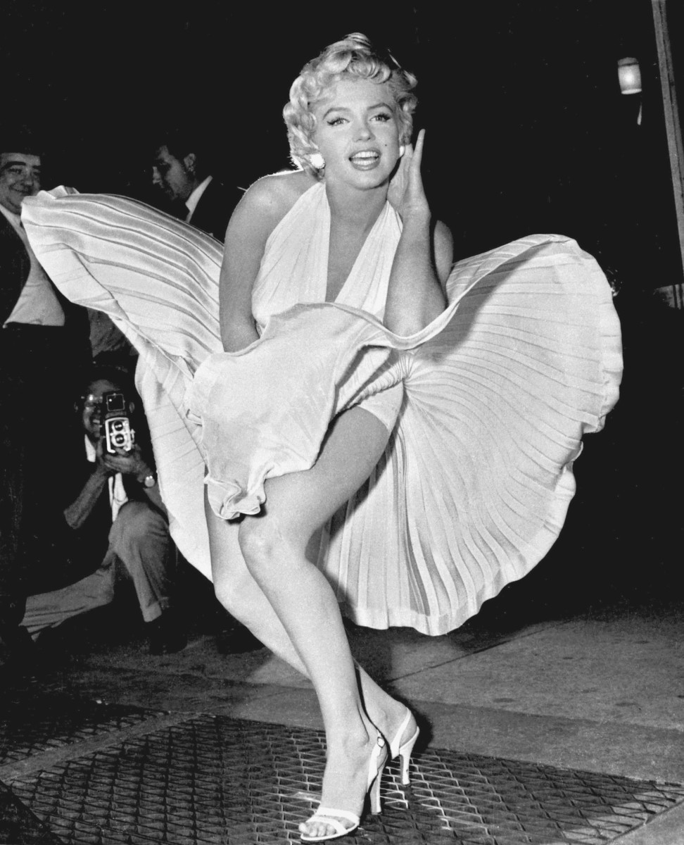 Marilyn Monroe wearing the former world-record dress in The Seven Year Itch on the streets of New York. When she stopped filming this famous scene over the subway grate, she posed for the reporters and photographers who were covering the film shoot.
