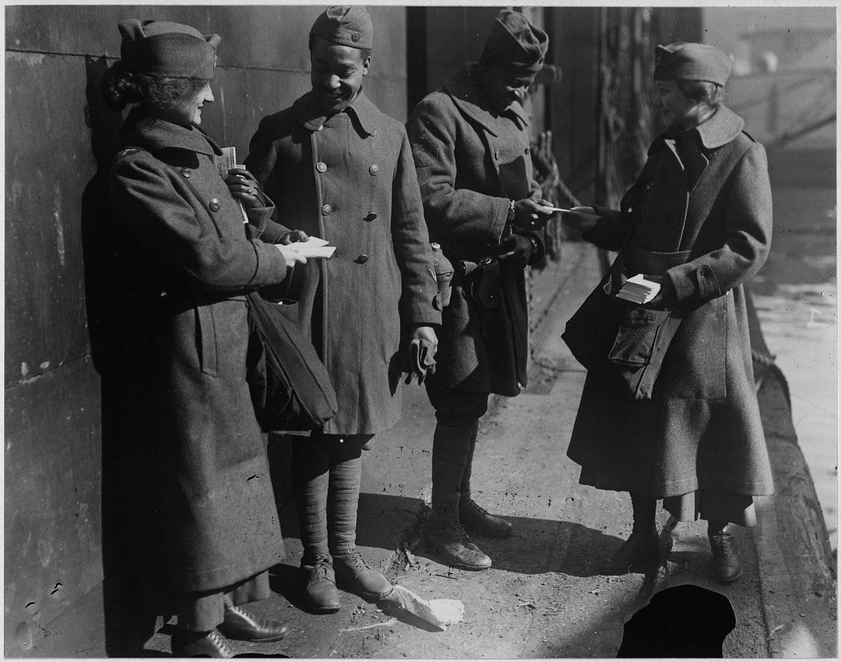Dressed in long wool coats and hats, two Donut Lassies hand out doughnuts to two returning soldiers of the 351st Field Artillery, Louisville, Kentucky, 1919.