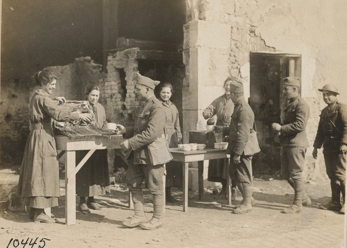Amidst a backdrop of ruins, Salvation Army volunteers Gladys and Irene McIntyre, Myrtle Turkington and Stella Young serve doughnuts, coffee and smiles to soldiers, 26th Division, Ansonville, France, April 1918.