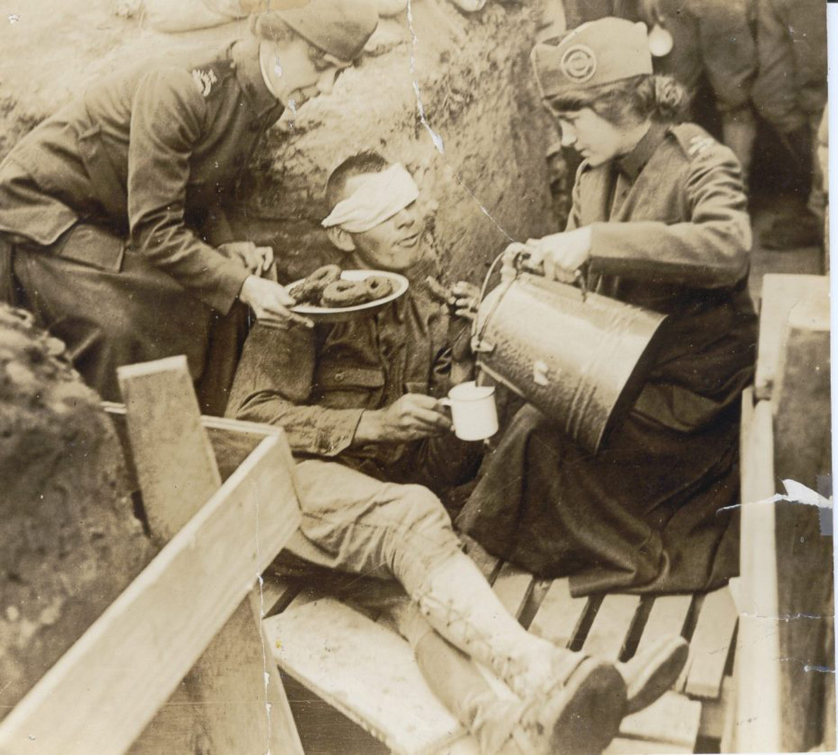 Donut Lassies serve coffee and doughnuts to a wounded soldier at the front line.