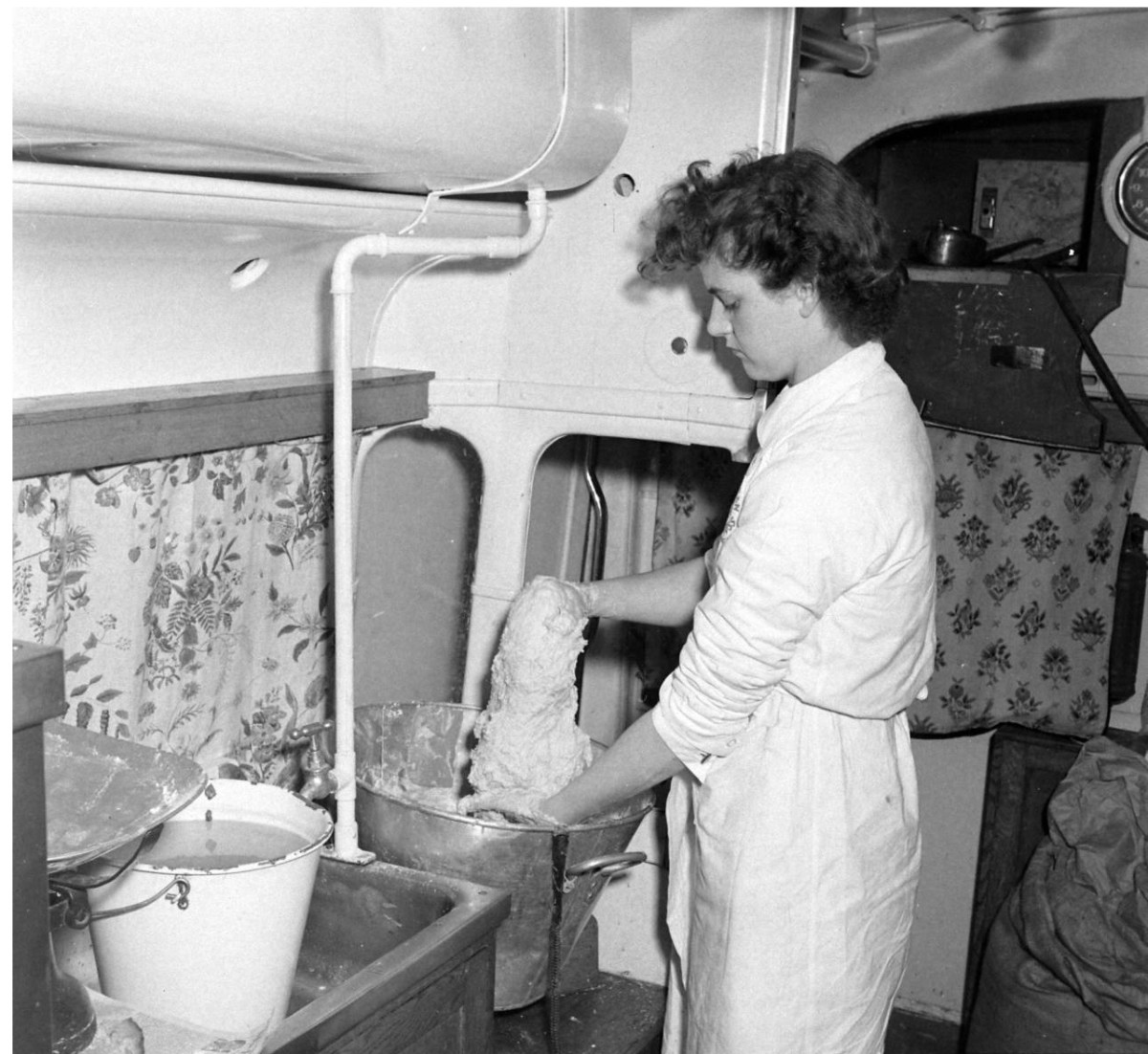 A Red Cross volunteer in a Clubmobile gets the dough ready to fry up another batch of doughnuts.