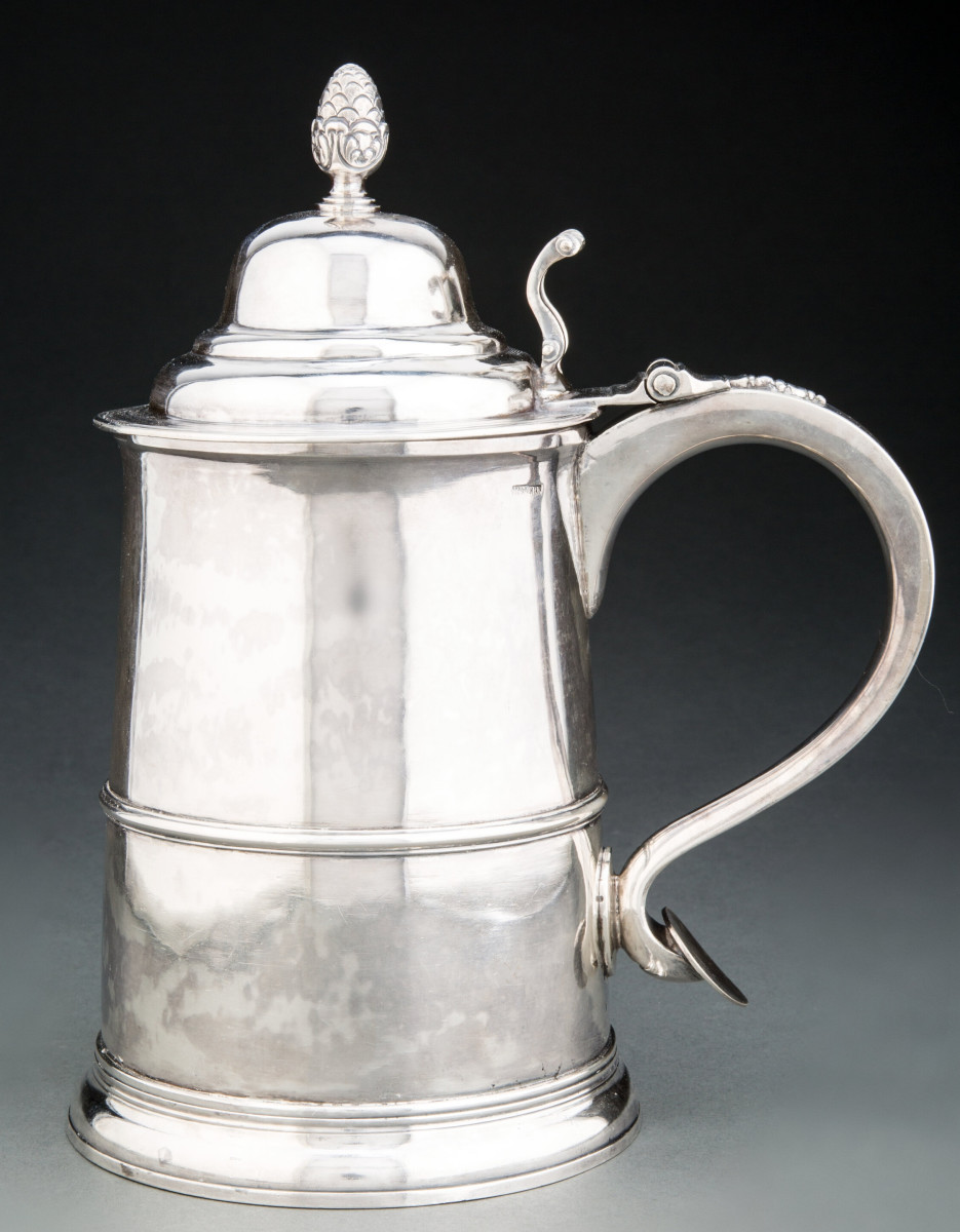 """The top lot of the sale was this tankard by Paul Revere, Jr., Boston, circa 1790, that sold for $112,500. The 10"""" x 8"""" tankard has a tapered body, horizontal mid-band, and C-scroll handle with scrolled openwork thumb piece to baluster drop below three-knuckle hinge, later pineapple-form finial on domed cover."""